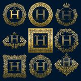 Vintage monograms set of H letter. Golden heraldic logos in wreaths, round and square frames.  Stock Images