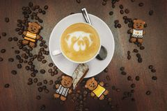 Vintage mood, Cappuccino on top with bear latte art lay on brown table, love coffee latte. Vintage mood, Cappuccino on top with heart latte art lay on black Stock Photo