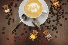Vintage mood, Cappuccino on top with bear latte art lay on brown table, love coffee latte. Vintage mood, Cappuccino on top with heart latte art lay on black Royalty Free Stock Images