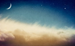 Vintage Moon. A crescent moon and stars rising above misty fog and clouds.  Image is done in retro colors and exhibits a pleasing paper grain and texture at 100 Royalty Free Stock Photos