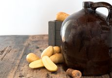 Vintage moonshine jug on a rustic wooden table with potatoes and corn cob cork. For distilling hard liquor stock photography