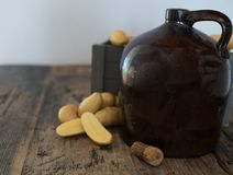 Vintage moonshine jug on a rustic wooden table with potatoes and corn cob cork. For distilling hard liquor stock image