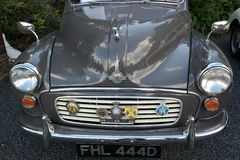 Vintage morris car detail. Vintage morris minor car grey bonnet and front grille headlights bumper AA RAC and other racing badges Stock Photo