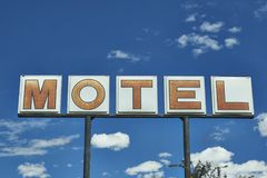 Vintage MOTEL sign with blue sky and puffy clouds. Classic americana MOTEL sign. roadside motel advertising sign with a blue sky. red letters on a white Royalty Free Stock Photo