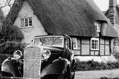 Vintage Motor Car outside a Thatched Cottage Stock Photo