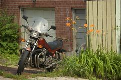 Vintage motorcycle. Staying in a messy backyard stock image