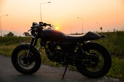 Vintage motorcycle cafe racer style. With sunset scene stock photos