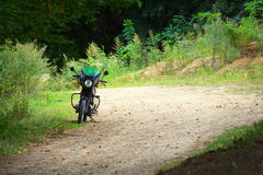 Vintage motorcycle in the forest. Old (vintage) motorcycle on a forest trail Stock Photography