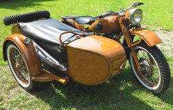 Vintage motorcycle with sidecar parked on grass Royalty Free Stock Photos
