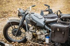 Old Vintage Motorcycle German troops. A vintage motorcycle from the times of the Second World War in gray with a stroller stands in the field. German forces Royalty Free Stock Image