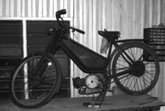 Vintage motorized bicycle/ early motorcycle. A vintage motorized bicycle/ early motorcycle awaits restoration in a Malaysian workshop royalty free stock image