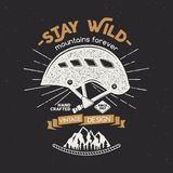 Vintage mountaineering badge. Climbing logo, vintage emblem. Climb gear - helmet and text Stay wild - mountains forever. Retro t shirt rough design Royalty Free Stock Image