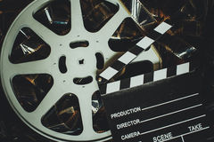 Vintage movie background, reel filmstrip and clapper board. Vintage movie background in cinematic color effect, texture of unrolled 35mm filmstrip reel and royalty free stock photos