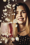 Vintage movie going girl watching arty film. Vintage cinema audience girl smiling when watching arty film in a creative fall of popcorn. Double movie pass Royalty Free Stock Photography