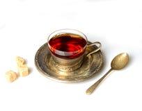Vintage mug with fragrant tea on a metal saucer, sugar, a teaspoon on a white background Stock Image