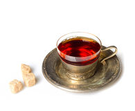 Vintage mug with fragrant tea on a metal saucer and sugar on a white background Royalty Free Stock Photo