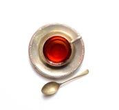 Vintage mug with fragrant tea on a metal saucer and teaspoon on a light background Stock Photography