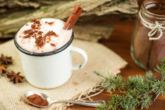 Vintage mug of hot chocolate with cinnamon sticks over rustic background. Stock Photos