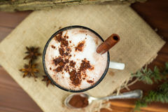 Vintage mug of hot chocolate with cinnamon sticks over rustic background. Stock Photo