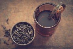 Vintage mug of tea and rustic metal cup of dry tea leaves. Royalty Free Stock Image