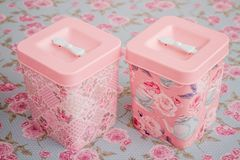 Vintage Multi Purpose Storage Containers with  Floral Pattern. On floral background Royalty Free Stock Photography