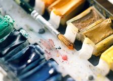 Vintage multicolor watercolor with cuvettes and a paintbrush royalty free stock photo