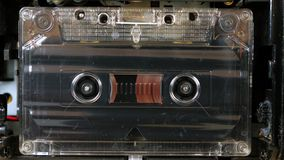 Movement of reels with magnetic tape in an old audio cassette. Vintage music audio player. Movement of reels with magnetic tape in an old audio cassette stock footage
