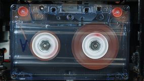 Movement of reels with magnetic tape in an old audio cassette. Vintage music audio player. Movement of reels with magnetic tape in an old audio cassette stock video