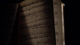 Vintage music notes with ray of light on black, cam moves top down. Vintage music notes with ray of light black background, cam moves top down stock footage