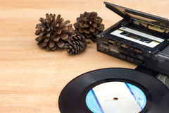 Vintage music player. Old gramophone record, Old portable taps player, Cassette, Dry pine flower on wood background stock photography
