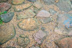 Vintage nature cobblestone and pebbles pavement in disorganized. Arrangement pattern background. Paving blocks made of nature asymmetrical stone background Royalty Free Stock Image