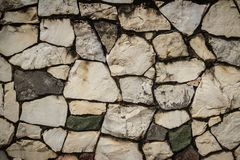 Vintage nature cobblestone wall in disorganized arrangement patt. Ern background. Fence wall made of nature asymmetrical stone background Royalty Free Stock Photo