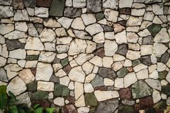 Vintage nature cobblestone wall in disorganized arrangement patt. Ern background. Fence wall made of nature asymmetrical stone background Stock Photo