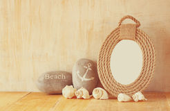 Vintage nautical frame from ropes and natural seashells on wooden table Stock Images