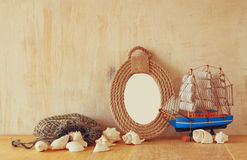 Vintage nautical frame from ropes, wooden boat and natural seashells on wooden table.  Stock Images