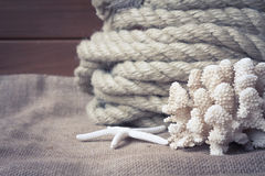 Vintage nautical still life with rope, starfish and coral on old wooden background Stock Image