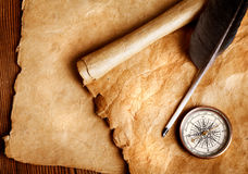 Vintage Navigation Items. A set of old navigation objects: quill pen, compass & paper scroll, on a wooden table Stock Photography