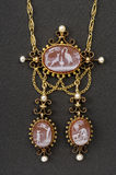 Vintage necklace on black. Old gold necklace depicting three fables of Jean de La Fontaine royalty free stock photos