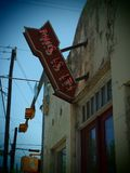 Vintage Neon This Is It Arrow Sign. A vintage arrow shaped neon sign reading This Is It on a rundown building in Austin, Texas royalty free stock photo