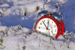 Vintage new year clock alarm-clock on snow. Vintage new year clock alarm-clock on fresh december winter snow. New year concept Royalty Free Stock Photo
