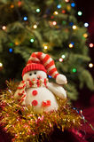 Vintage New Year snowman on the background of the Christmas tree Royalty Free Stock Photo