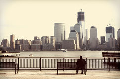 Vintage New York City. Solitary man on a boardwalk looking at the New York City skyline; vintage feel Royalty Free Stock Photos