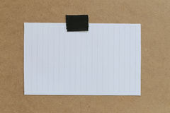Vintage of note paper on brown background and copy specs. Royalty Free Stock Images