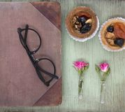 Vintage notebook mock up for artwork with pink roses and cakes. Place for text. Fresh flowers and black glasses. Royalty Free Stock Photography