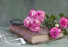 Vintage notebook mock up for artwork with pink roses. Place for text. Fresh flowers ans white headphones. Vintage notebook mock up for artwork with pink roses royalty free stock photo