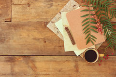 Vintage notebook, old paper and wooden pencil next to cup of coffee over wooden table. ready for mockup Royalty Free Stock Photo