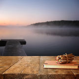 Vintage notebook and stack of wooden colorful pencils on wooden texture table in front of calm foggy lake view at sunset.  Stock Image