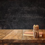 Vintage notebook and stack of wooden colorful pencils on wooden textures table against chalkboard background.  Stock Image