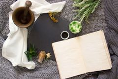 Vintage notebook surrounded by herbs, alchemy appliances, potions and ingredients lies on natural slate slab wooden table. Halloween occultism background. Flat royalty free stock image