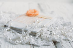Vintage notebook on white table. Vintage handmade Notepad on a white table cloth and beads from pearls Royalty Free Stock Photography